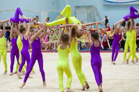 Tyumen, Russia - May 27, 2018: Priboy superiority of Olympic reserve school for children and young people on rhythmic gymnastics in Stroymash sports complex. Show program of young gymnasts team Stock Photo - 128834978
