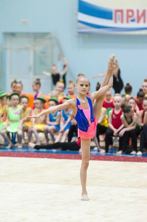Tyumen, Russia - May 27, 2018: Superiority of school for children and young people of the Olympic reserve Surf on rhythmic gymnastics. Sports complex Priboy. Young pretty girl shows own skill in exercise with ball