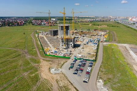 Tyumen, Russia - July 15, 2015: Aerial view on lifting cranes on residental house construction site. Three athletes housing estate