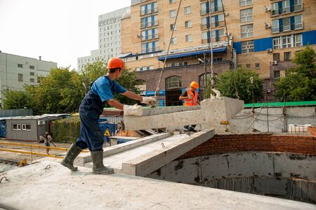 Tyumen, Russia - July 31, 2013: JSC Mostostroy-11. Construction of a 18-storeyed brick residental house at the intersection of streets of Nemtsov and Tsiolkovsky. Builders on construction Editorial