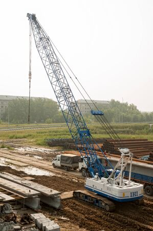 Tyumen, Russia - July 31, 2013: JSC Mostostroy-11. Bridge construction for outcome of the Tobolsk path and Bypass road round Tyumen. Construction crane and other equipment at bridge building