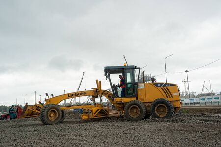 Tobolsk, Russia - July 15. 2016: Sibur company. Construction of plant on processing of hydrocarbonic raw materials. Grader leveling gravel on construction site in rainy weather