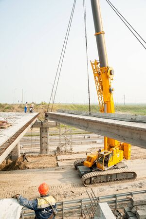 Tyumen, Russia - July 31, 2013: JSC Mostostroy-11. Bridge construction for outcome of the Tobolsk path and Bypass road round Tyumen. Crane working on bridge construction to pass through it vehicles