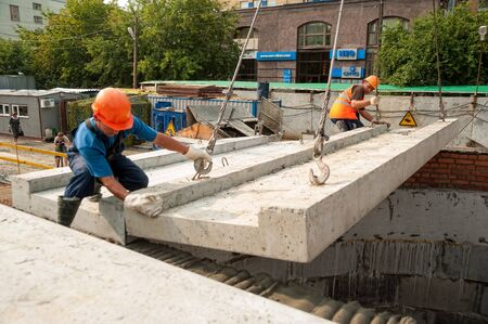 Tyumen, Russia - July 31, 2013: JSC Mostostroy-11. Construction of a 18-storeyed brick residental house at the intersection of streets of Nemtsov and Tsiolkovsky. Builders during working process