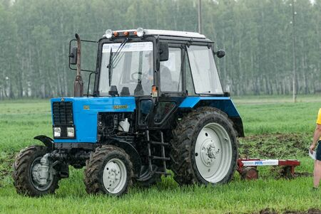 Tyumen, Russia - June 24, 2016: The 5th open championship of Russia on a plowed land. Young operator plows the site on Belarus tractor in rainy weather
