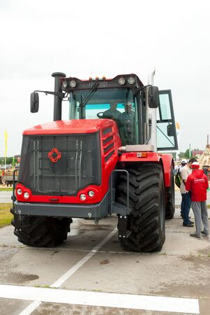 Tyumen, Russia - June 24, 2016: The 5th open championship of Russia on a plowed land. The tractor operator on a tractor rolls visitors