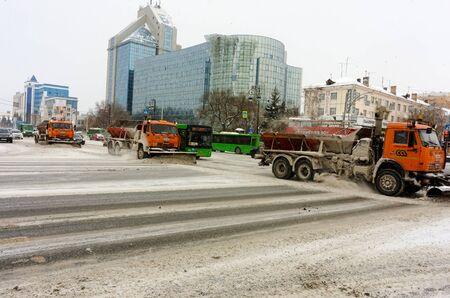 Tyumen, Russia - December 17, 2018: Respubliki street with Gazprom building. Snowplows removing snow in street after blizzard