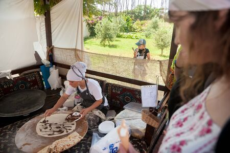 Turkler, Turkey - July 27, 2018: Senza hotel tent. Turkish woman makes a traditional national dish - a baked flat pancake Gozleme