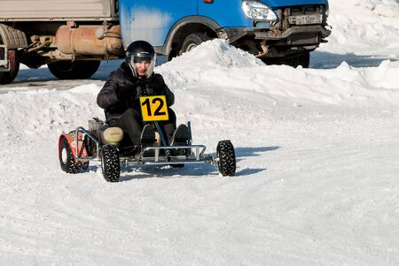 Tyumen, Russia - February 22, 2015: Ice autodrome Ice cult on Alebashevo lake. Man is driving Go-kart with speed on karting track Editorial