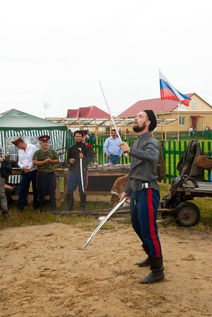 Tyumen, Russia - June 24, 2016: The 5th open championship of Russia on a plowed land. Cossack shows skill of sabre possession Sajtókép