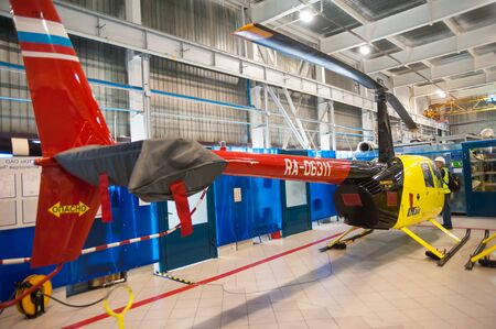 Tyumen, Russia - June 5, 2019: Aircraft repair helicopter UTair Engineering plant. Robinson R44 helicopter during maintencance and repair at the service hangar Editoriali