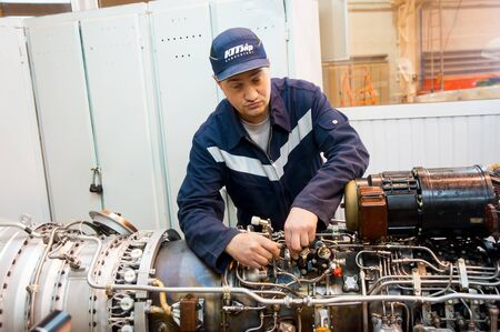 Tyumen, Russia - June 5, 2019: Aircraft repair helicopter UTair Engineering plant. Worker maintaining engine of Mi-8 helicopter