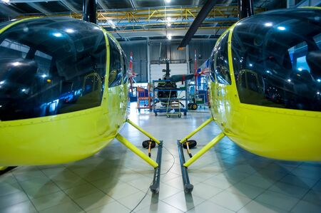 Tyumen, Russia - June 5, 2019: Aircraft repair helicopter UTair Engineering plant. Robinson R44 helicopters during maintencance and repair at the service hangar
