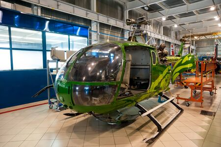 Tyumen, Russia - June 5, 2019: Aircraft repair helicopter UTair Engineering plant. Eurocopter helicopter during maintencance and repair at the service hangar Editoriali