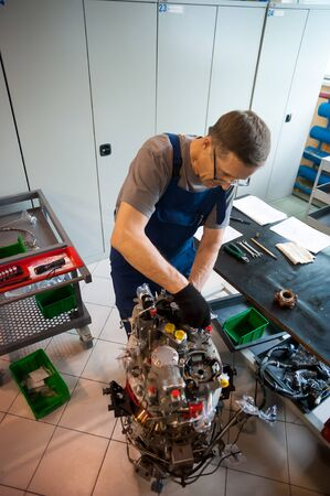 Tyumen, Russia - June 5, 2019: Aircraft repair helicopter UTair Engineering plant. Worker maintaining engine of import helicopter
