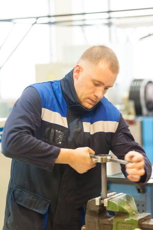 Tyumen, Russia - June 5, 2019: Aircraft repair helicopter UTair Engineering plant. Technician at machine maintenance working with wrench Editorial
