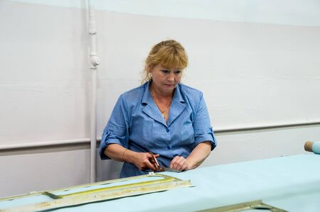 Tyumen, Russia - June 5, 2019: Aircraft repair helicopter UTair Engineering plant. Woman sticks together an element of an internal covering of the helicopter