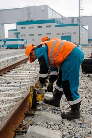 Tobolsk, Russia - July 15. 2016: Sibur company. The worker establishes jack for lifting rails for the purpose of repair of a railroad body Editorial