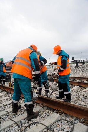 Tobolsk, Russia - July 15. 2016: Sibur company. Denisovka railway station. Railway workers repairing rails in rainy weather