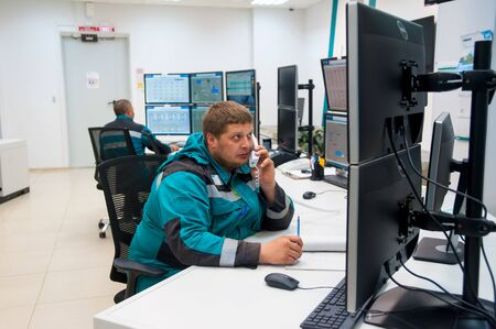 Tobolsk, Russia - July 23. 2019: Sibur company. Plant on processing of hydrocarbonic raw materials. Man in industrial control room using phone to give instructions