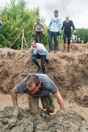 Tyumen, Russia - August 8, 2015: Steel Character extrim race on Krugloe lake. Gagarin park in Cape district. Obstacle - Mud hole. Selection stage