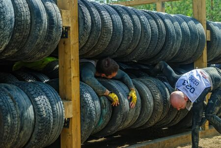 Tyumen, Russia - June 11, 2016: Race of Heroes project on the ground of the highest military and engineering school. Athlete moves between old tires. Human birth stage