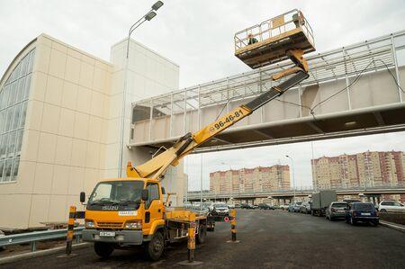 Tyumen, Russia -August 13, 2019: Construction of a highway junction on Fedyuninsky street. Builder on autotower make construction work on bridge