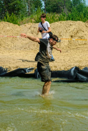 Tyumen, Russia - June 11, 2016: Race of Heroes project on the ground of the highest military and engineering school. Sportsmen jumps in water 報道画像