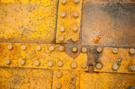 Antique rusty metal square nuts locked with rust and corrosion on old heavy duty bolts holding a thick and corroded vintage industrial steel plate structure as a retro grunge background Stock Photo