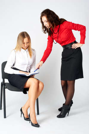 Two young attractive businesswomen having informal meeting over white background
