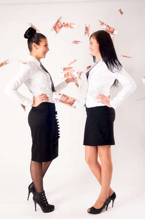 Two young business ladies argue because of paper money. Isolated over white background Stock fotó - 153219418