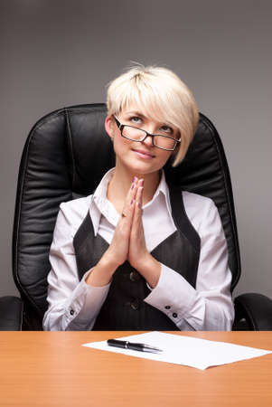 Young attractive business woman prays behind table Banco de Imagens