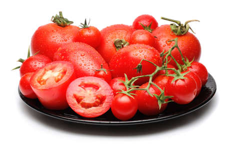 black dish: Fresh tomatoes of different variety on black dish isolated on white
