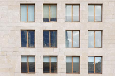 many windows: Beige stone wall with many windows close up Stock Photo