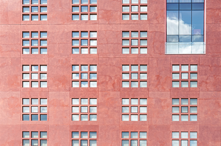 many windows: Modern red stone wall with many windows close up