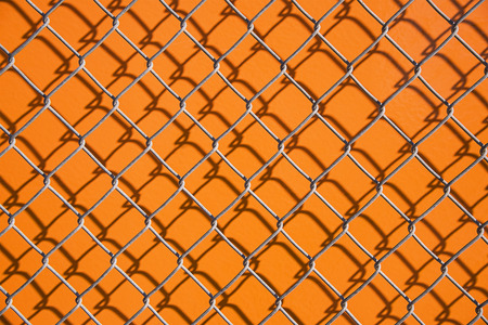 wire fence: Wire fence on orange background close up