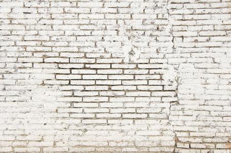 Vecchio muro di mattoni con la fine bianca di struttura del fondo della pittura su