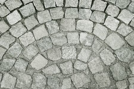 Old grey stone pavement background texture close up