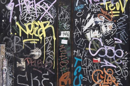 Black wall with colorful graffiti background close up