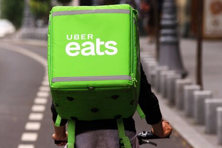 Bucharest, Romania - August 01, 2018: An Uber Eats courier delivers food in Bucharest, Romania.