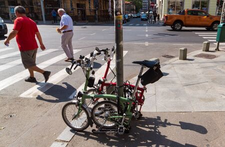 Bucharest, Romania - July 31, 2019: Two folding bicycles locked on a pole are parked near a crosswalk in downtown Bucharest.