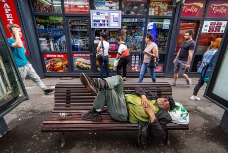 Bucharest, Romania - June 12, 2019: An old man looking like a homeless is sleeping on Charles de Gaulle bus station banch in Primaverii neighborhood, the richest in Bucharest. For editorial use only.