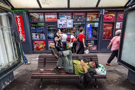 Bucarest, Roumanie - 12 juin 2019 : un vieil homme ressemblant à un sans-abri dort sur le banc de la gare routière Charles de Gaulle dans le quartier de Primaverii, le plus riche de Bucarest. Pour un usage éditorial uniquement. Éditoriale