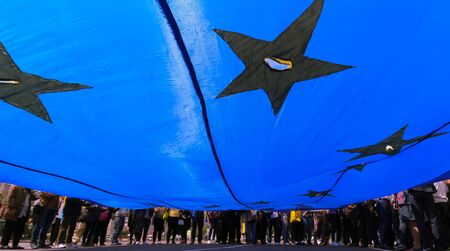 Bucharest, Romania - May 18, 2019: Supporters of the National Liberal Party hold a European Union flag at the rally for the European Parliamentary elections and for the anti-corruption referendum. Editöryel