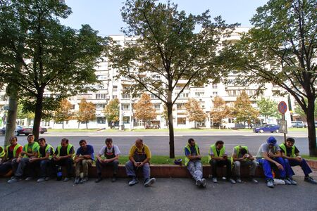 Bucharest, Romania - September 10, 2018: Several construction workers are relaxing sitting on a curb while smoking or drinking coffee or soft drinks during lunch break in Bucharest.
