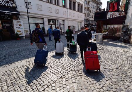 Bucharest, Romania - April 04, 2019: A group of tourists carrying suitcases walks on the Selari Street, in downtown Bucharest, Romania. This image is for editorial use only.