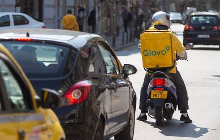Bucharest, Romania - April 03, 2019: A Glovo food delivery courier delivers food in Bucharest, Romania. This image is for editorial use only Reklamní fotografie - 137979572