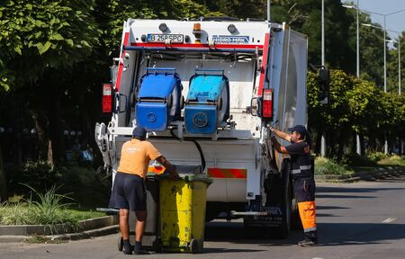 Bucharest, Romania - August 29, 2019: Two sanitation workers empty the trash cans in a garbage car, in Bucharest Editorial