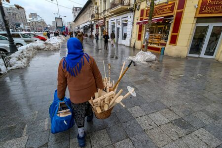 Bucharest, Romania - January 15, 2019: An elderly villager woman carries two baskets with traditional wooden tools for cooking.