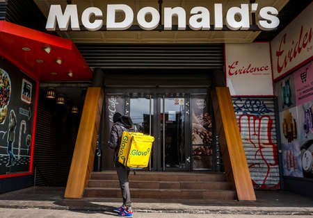 Bucharest, Romania - March 25, 2020: A Glovo food delivery courier stands in front of the oldest McDonald's restaurant in Romania temporary closed during the state of emergency due to coronavirus. Editorial